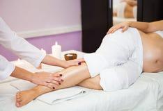 Ung gravid kvinna som kopplar av med handbenmassage på skönhetsp royaltyfria bilder
