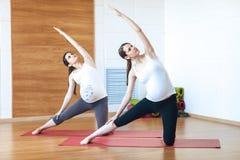 Ung gravid modell för kondition två i sportswearen som gör yoga, pilates som utbildar, utfallövning, Utthita Parsvakonasana, förd Arkivbild