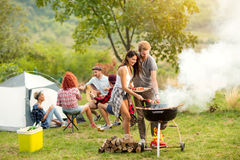 Ung grillfest för kvinnlig- och manparbakning Fotografering för Bildbyråer