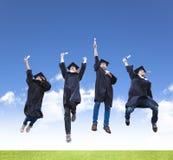 ung grupp av avläggande av examenstudenter som tillsammans hoppar Arkivbilder