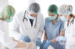 Ung grupp av doktorer som gör operation royaltyfria bilder