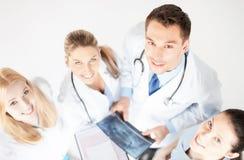 Ung grupp av doktorer som ser röntgenstrålen royaltyfri foto