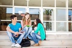 Ung grupp av studenter i universitetsområde Arkivfoto