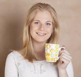 Ung gullig blond flicka som dricker upp nära kaffe på Arkivbild