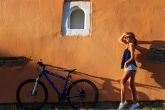 Ung gullig dam som poserar med cykeln nära väggen fotografering för bildbyråer