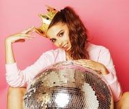 Ung gullig diskoflicka på rosa bakgrund med den diskobollen och kronan Arkivbild