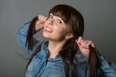 Ung gullig flicka som rymmer hennes hår Arkivfoto
