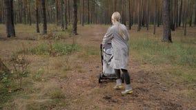 Ung gullig mamma som går i parkera med en sittvagn Lyssna till musik och dansa