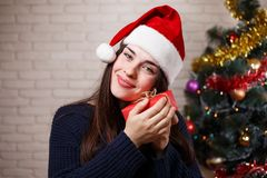 Ung gullig nöjd kvinna i jultomtenlock med en gåvaask i hand n Royaltyfria Foton