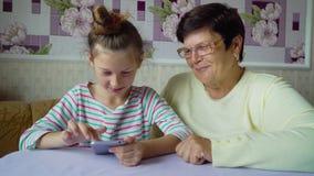 Ung gullig sondotterundervisningfarmor hur man använder smartphonen hemma lager videofilmer
