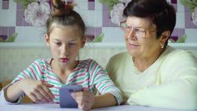 Ung gullig sondotterundervisningfarmor hur man använder smartphonen hemma arkivfilmer