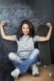 Ung gullig tonårs- flicka i klassrum på svart tavlaplacering på att le för tabell Fotografering för Bildbyråer