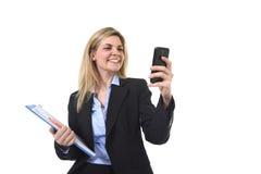 Ung härlig affärskvinna för blont hår som använder internet app på för för kontorsmapp och penna för mobiltelefon som hållande le fotografering för bildbyråer