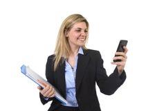 Ung härlig affärskvinna för blont hår som använder internet app på för för kontorsmapp och penna för mobiltelefon som hållande le arkivbild