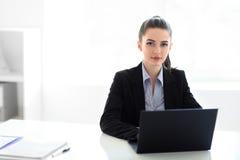 Ung härlig affärskvinna med bärbara datorn i kontoret Royaltyfri Fotografi