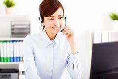 Ung härlig affärskvinna med hörlurar med mikrofon i regeringsställning Arkivfoton