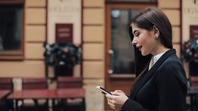 Ung härlig affärskvinna som använder smartphonen och går på den gamla gatan Henne som surfar internet Begrepp: nytt stock video