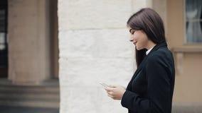 Ung härlig affärskvinna som använder smartphonen och går på den gamla gatan Henne som surfar internet Begrepp: nytt lager videofilmer