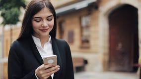 Ung härlig affärskvinna som använder smartphonen och går på den gamla gatan Henne som surfar internet Begrepp: nytt arkivfilmer