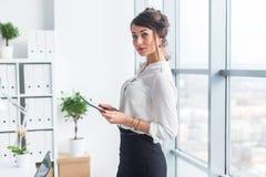 Ung härlig affärskvinna som i regeringsställning använder minnestavlan med internet, läser och överför meddelanden, le som ser arkivbilder