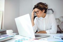 Ung härlig affärskvinna som i regeringsställning arbetar med bärbara datorn på arbetsplatsen Arkivfoto