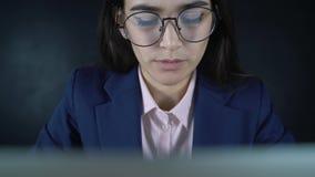 Ung härlig affärskvinna som sitter på en tabell med en bärbar dator I aftonen arbetar en kvinnlig freelancer avlägset stock video