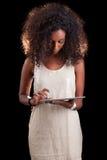Ung härlig afrikansk amerikankvinna som använder en känsel- minnestavlaPC Royaltyfri Bild