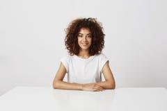 Ung härlig afrikansk flicka i exponeringsglas som ler se kameran som sitter över vit bakgrund fotografering för bildbyråer
