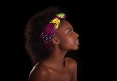 Ung härlig afrikansk kvinnastående som tillbaka isoleras över svart royaltyfria foton