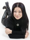 Ung härlig asiatisk flicka i svart på en ljus bakgrund Royaltyfria Foton