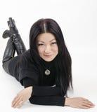 Ung härlig asiatisk flicka i svart på en ljus bakgrund Royaltyfri Foto