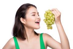 Ung härlig asiatisk kvinna som äter nya druvor som isoleras på whit arkivbild