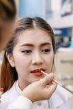 Ung härlig asiatisk kvinna som applicerar smink av sminkkonstnären fotografering för bildbyråer
