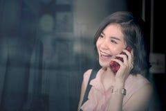 Ung härlig asiatisk kvinna som ler och använder smartphonen Royaltyfri Foto