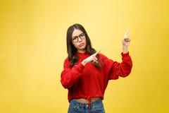 Ung härlig asiatisk kvinna som pekar till copyspace, på gul bakgrund arkivfoto