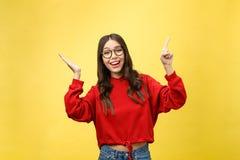 Ung härlig asiatisk kvinna som pekar till copyspace, på gul bakgrund arkivbild
