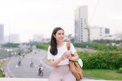 Ung härlig asiatisk kvinna som utomhus använder smartphonen Royaltyfri Fotografi