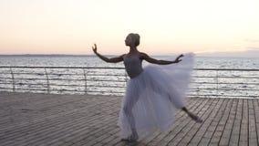 Ung härlig ballerinakjol för iklädd vit för ballerina som behagfullt dansar på hennes pointebalettskor Hoppa och att utföra lager videofilmer