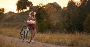 Ung härlig blond flicka i sommar i klänning och hatt som går på vägen med cykeln och blommor i ultrarapid stock video