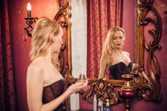 Ung härlig blond flicka och hennes reflexion i en stor gammal budoarspegel i det lyxiga rummet royaltyfri foto