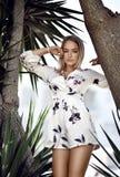 Ung härlig blond flicka som poserar i tropisk skogsemesterort i den vita tillfälliga klänningen royaltyfri foto