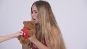 Ung härlig blond kvinna i bikini med att agera för nallebjörn som är lik ett barn lager videofilmer