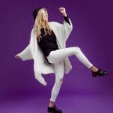 Ung härlig blond kvinna i trendig hatt Ge en spark fotografering för bildbyråer