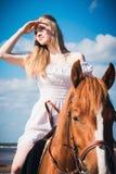 Ung härlig blond kvinna och en häst Arkivfoto