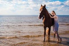 Ung härlig blond kvinna och en häst Arkivfoton