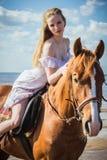 Ung härlig blond kvinna och en häst Royaltyfria Bilder