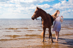 Ung härlig blond kvinna och en häst Fotografering för Bildbyråer