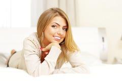 Ung härlig blond kvinna som ligger på sängen Arkivbilder