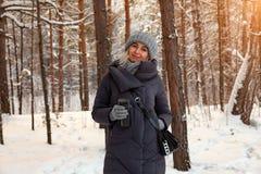 Ung härlig blondin i drinkar kaffe eller te för en stucken hatt, halsduk- och handskei den vinter snö-täckte skogen på solnedgång arkivfoton