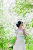 Ung härlig brud i en blomstra trädgård i vår Royaltyfri Bild